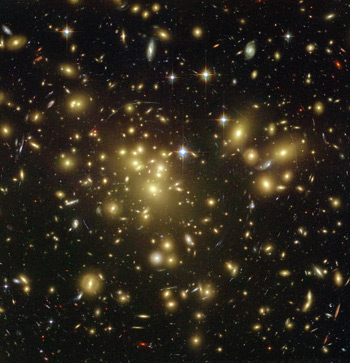 This image shows the galactic cluster Abell 1689, whose gravity distorts images of galaxies behind it (in the line of sight) through gravitational lensing. The mass obtained from lensing is far larger than the mass obtained from the luminous matter that is observed.