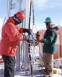 Two AMANDA investigators fasten a light detector to a cable, so the detector can be lowered into the hole melted in the Antarctic ice