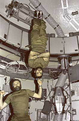 In the SkyLab orbiter, one astronaut balances another on his index finger. (photo courtesy of NASA)