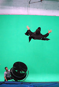 "Attached to wires and blown by a wind machine, Brian Greene ""flies"" through the air against a green screen background, which will be replaced in the editing process by footage of a city street scene. (Photo by Andrea Cross for WGBH)"