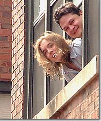 Anne and her husband, Sergio, leaning out the window of their home in Chicago.