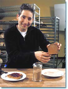 Brian Greene holding piece of bread.