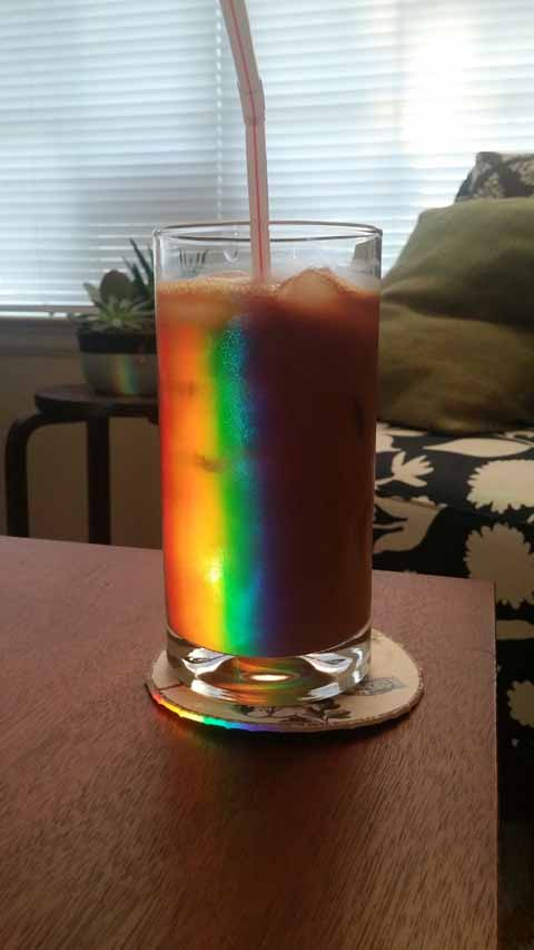Light bounces off a mirror and refracts through an empty glass to produce a rainbow of color