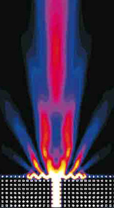 Corrugations in the surface of a simulated photonic crystal (bottom) coerce the upward-traveling light into a narrow beam as it leaves the crystal. This design may solve the problem of hooking up photonic crystals with conventional fiber optics. Image Credit: Phys. Rev. B 69, 121402 (2004)